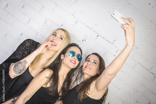 Poster Attraction parc Party girls. Three women taking a selfie on a white wall