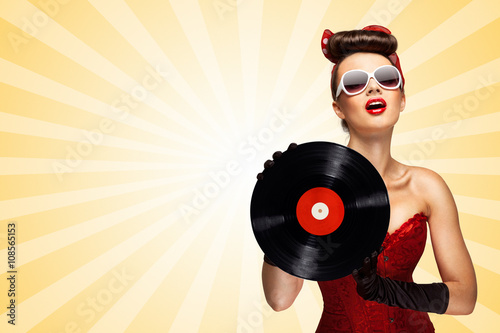 Fotografie, Obraz Retro play / Vintage photo of glamorous pinup girl wearing long gloves and dressed in a red sexy corset, holding LP vinyl record on colorful abstract cartoon style background
