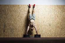 Bodybuilder Doing Handstand At The Wall In The Gym