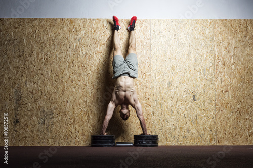 Valokuva Bodybuilder doing handstand at the wall in the gym