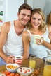 Loving couple having coffee at breakfast table in house