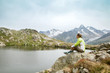 canvas print picture - woman sitting on rock and looking at mountain lake