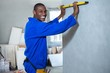 Happy handyman measuring a wall with spirit level