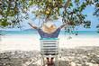 Woman sitting on a beach chair under a tree enjoying a summer da