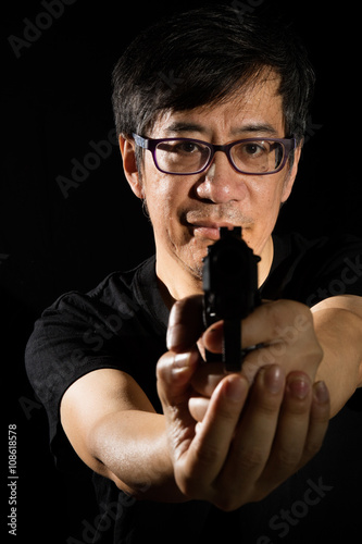 Asian Chinese Man Holding a Gun - Buy this stock photo and explore
