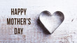 Mothers day composition. Heart shape cookie cutter. Wooden backg