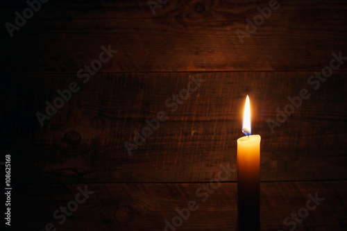 Photo candle on old wooden background