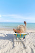 Girl relaxing on beach chair while using mobile phone