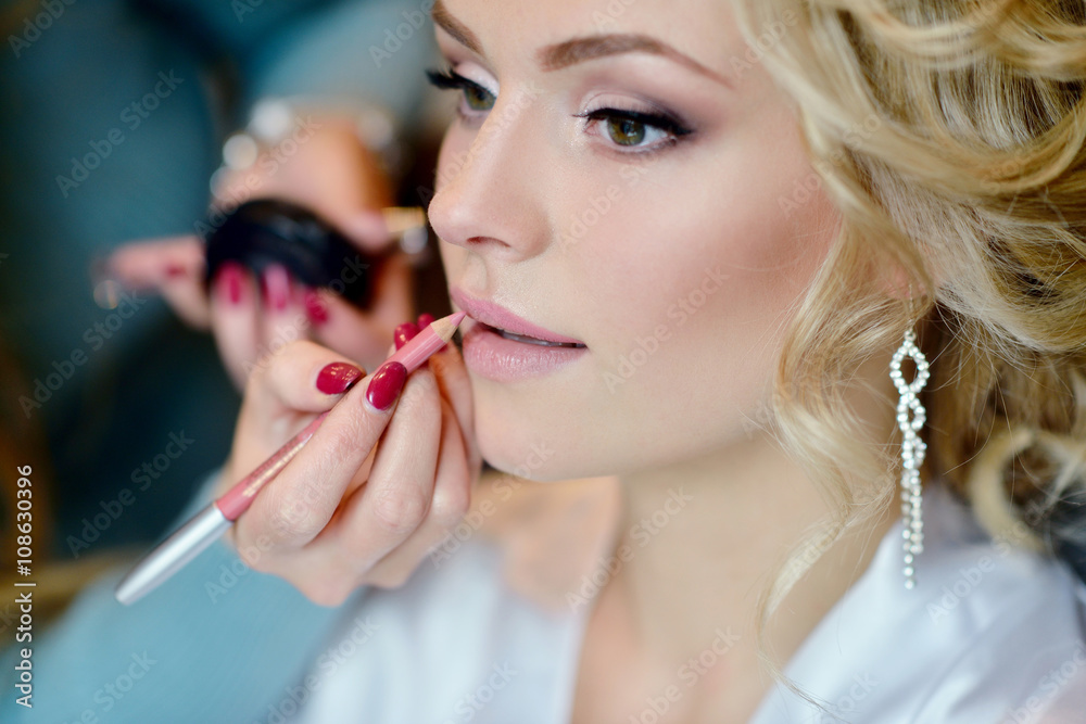 Fototapety, obrazy: Wedding makeup artist making a make up for bride. Beautiful sexy model girl indoors. Beauty woman with curly hair. Female portrait. Bridal morning of a cute lady. Close-up hands near face