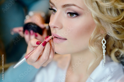 Photo Wedding makeup artist making a make up for bride