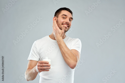 happy young man applying cream or lotion to face Wallpaper Mural