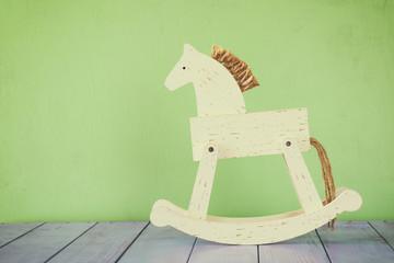 vintage rocking horse on wooden floor. retro filtered image