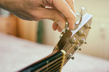 Tuning The Guitar. Fingers Are Turning The Tuning Peg On The Head Of Acoustic Guitar. Authentic Shot With Blurred Room In The Background.