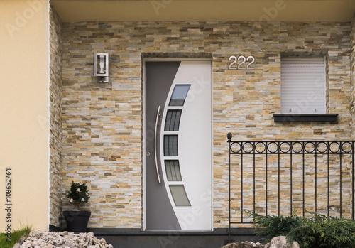 Fotografía  Moderner Eingang eines Hauses mit Haustür Fenster Geländer und Verblender aus Sa