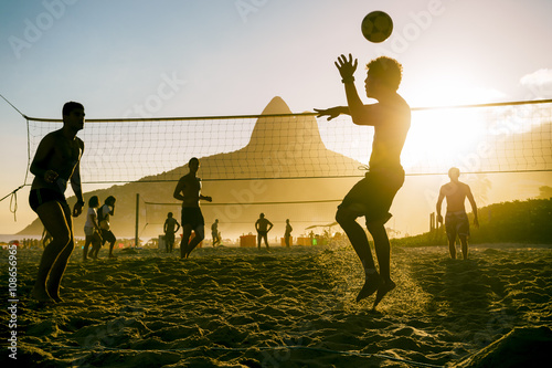 Valokuvatapetti Silhouettes of Brazilians playing beach futevolei (footvolley), a sport combinin