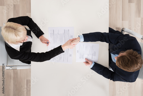 Businesspeople Shaking Hand At Desk Wallpaper Mural