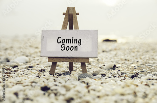 Valokuva conceptual image with word COMING SOON on white canvas frame with wooden tripod stand