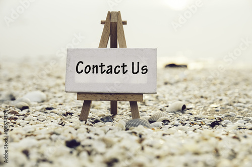 Fotografia, Obraz  conceptual image with word CONTACT US on white canvas frame with wooden tripod stand