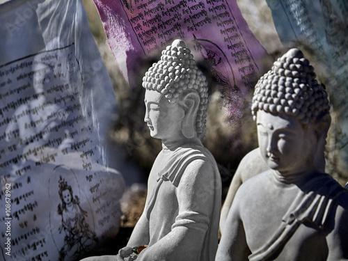 Fényképezés Buddhist figures made of cement sitting in meditation with prayer offerings and