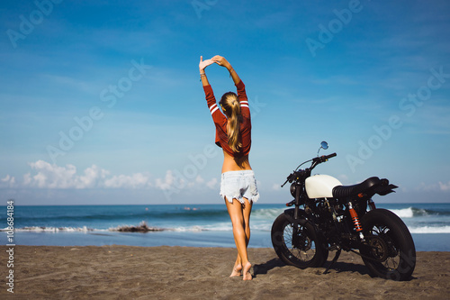 Obrazy na płótnie Canvas young pretty hipster girl Biker girl sitting on vintage custom motorcycle Biker girl sitting Outdoor lifestyle portrait. jeans short denim, fashion style