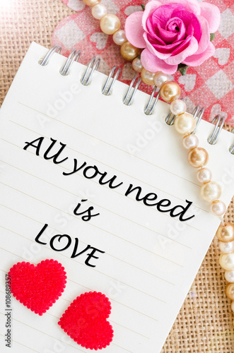 Photo  All you need is love on diary with red heart and rose.