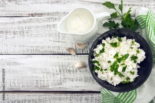 Tuinposter Zuivelproducten Cottage cheese with chives in black ceramic bowl