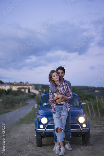 Deurstickers Toscane Young couple doing a road trip in Tuscany countryside in a vintage car