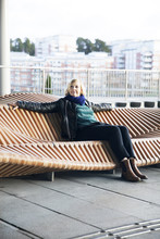 Woman Sitting On Modern Bench