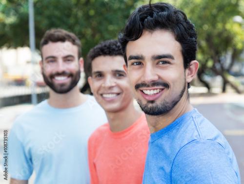 Fotografie, Obraz  Junger Latino mit zwei Freunden in der Stadt