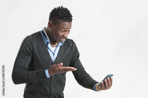 Fotografering  Young african American man using a mobile phone