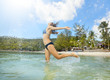 Happy young woman jumping in the sea water. Happiness, freedom a