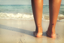 Leisure In Summer - Rear Of Beautiful Women Tan Relax On Beach With Tattoo On Foot. Retro Filter Effect
