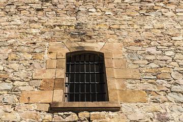 Fototapeta na wymiar Old stone wall with a latticed window