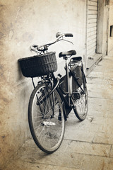 FototapetaVintage red bicycle with wicker basket at the street in Italy