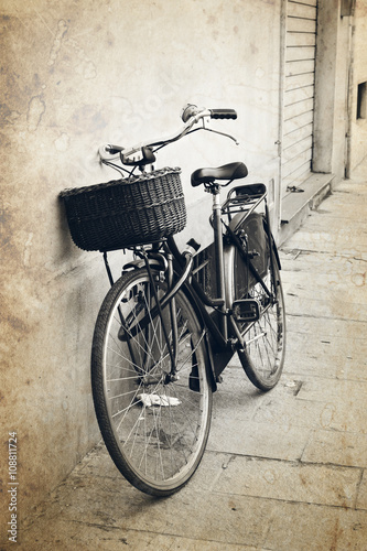 In de dag Fiets Vintage red bicycle with wicker basket at the street in Italy