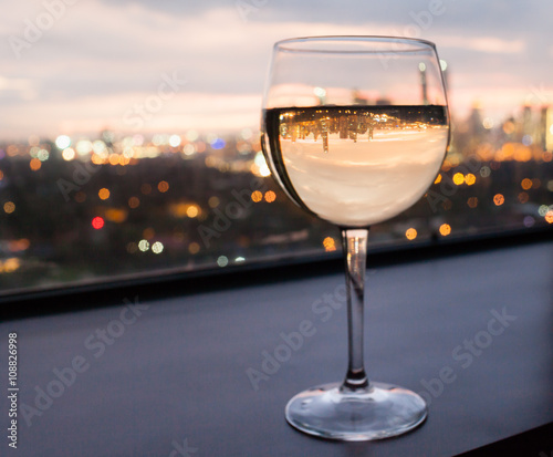 Glass of white wine in a restaurant with city view.