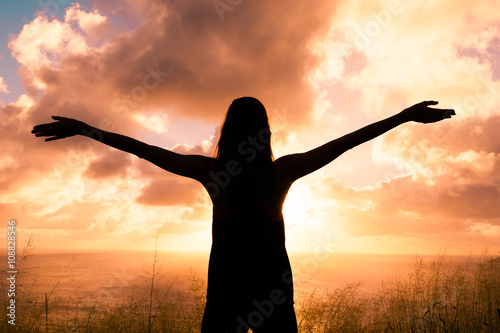 Fotografie, Obraz  Feeling happy and free. Young woman with her arms up in the air.