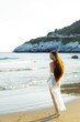 Woman with white dress walking on the beach