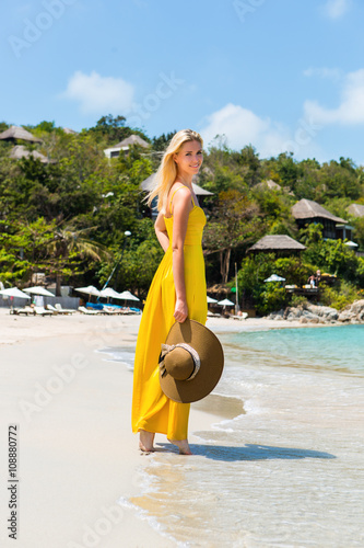 Carefree beautiful fashion blond girl in long yellow dress flying in wind  walking barefoot by sand of tropical shore and hold her beach straw hat. 5c67b1704852