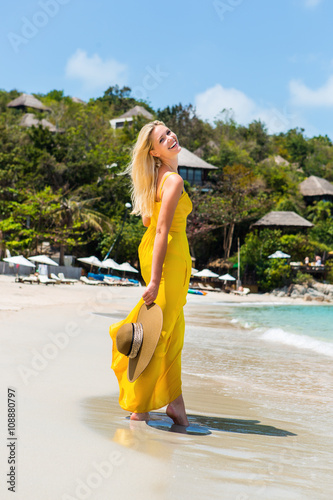 Carefree beautiful fashion blond girl in long yellow dress flying in wind  walking barefoot by sand of shore and hold her beach straw hat. Natural  woman ... 3837ee1873e7