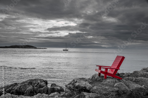 Staande foto Bleke violet Red chair contrasting with black and white ocean background.