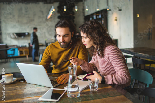 Young hipster male and female working laptop together in cafe Slika na platnu