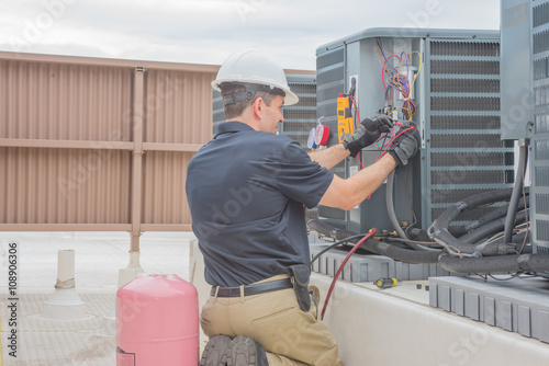 Fotomural  HVAC Tech Checking Condenser