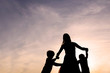Silhouette of Mother and Children Dancing at Sunset