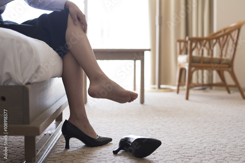 Valokuva  Woman is very tired and break off your shoes in the hotel room