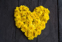 Yellow Chrysanthemum Flower  Shaped Like A Heart On Wood Backgro