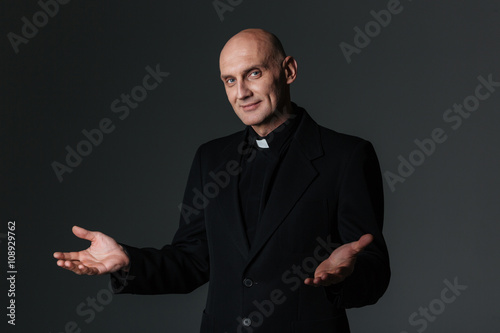 Obraz na płótnie Smiling priest standing and inviting you