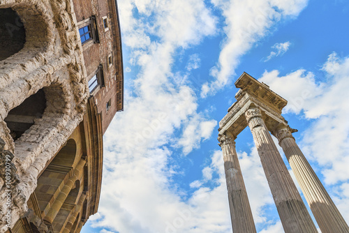 Beautiful view on the ancient Theatre of Marcellus( Teatro di Marcello ) and ruin of old building( antique columns and detail of the cornice ) next to it on the background of clouds Canvas Print