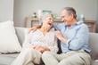 Leinwandbild Motiv Romantic senior couple laughing while sitting on sofa