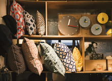 Pillows And Handmade Clocks In An Elegant Shop